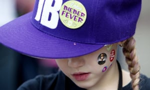 A young Justin Bieber fan wears stickers on her face .