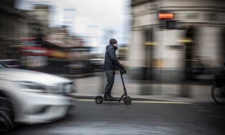 A man passes past Parliament Square on an electric scooter in London, England.