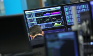 A trader works as screens show market data