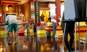 Voters fill out their ballots for the presidential primary election at a polling station inside Hua-Zang Si buddhist temple in San Francisco.