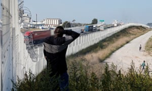 A man walks past the fence designed to stop migrants and refugees trying to reach Britain.