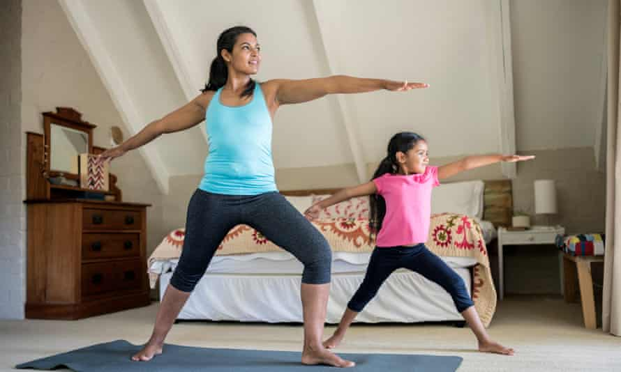 A mother and daughter practise yoga in a bedroom together
