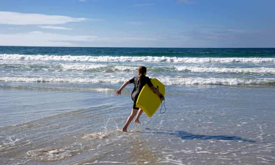 young girl wearing wetsuit running into sea with surfboard