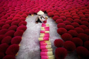 A woman collects incense sticks in a courtyard in the village of Quang Phu Cau on the outskirts of Hanoi.
