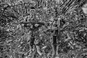 Angél, 14, left, and Daniel, 16, members of the ELN Che Guevara Front, pose for a picture at their camp in Chocó. The Che Guevara Front operates on the Pacific coast of Colombia patrolling important corridors to allow the export of cocaine