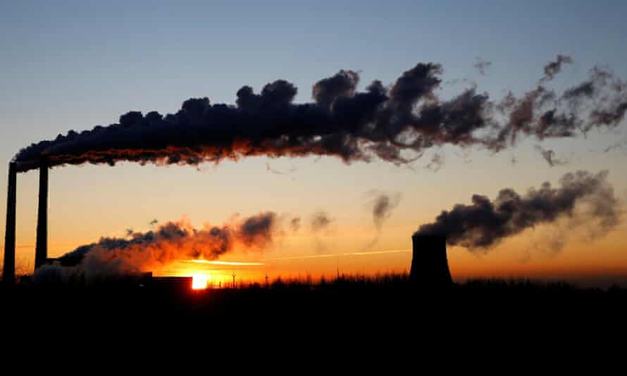 Sun rises behind the towers of a gas-fired power station.