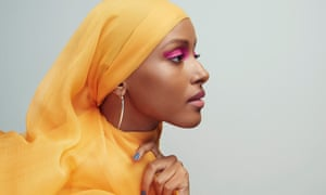 Shahira Yusuf, face in profile, heavy pink eyeshadow, a yellow/orange scarf around her head and neck