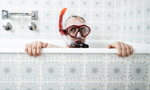 Photography of a man snorkeling in the bathtub. Soapbubbles coming out of the snorkel and flying around.
