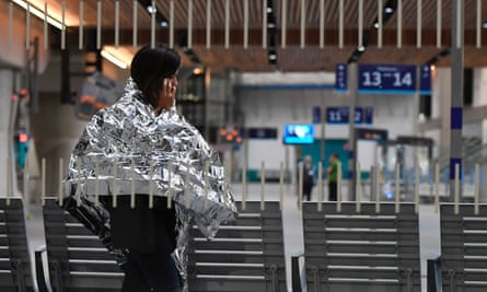 A woman wearing an emergency blanket talks on her phone at London Bridge train station.