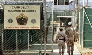 US military guards walk within Camp Delta military-run prison at the Guantánamo Bay US naval base.