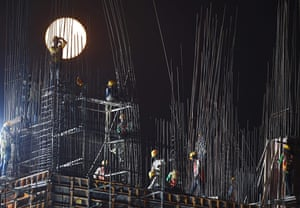 Construction labourers work as the moon rises over a building site in Kolkata. This will be its brightest occurrence for seven years