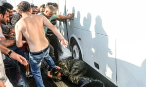 People beat a soldier on the ground after taking over a military position on the Bosphorus bridge