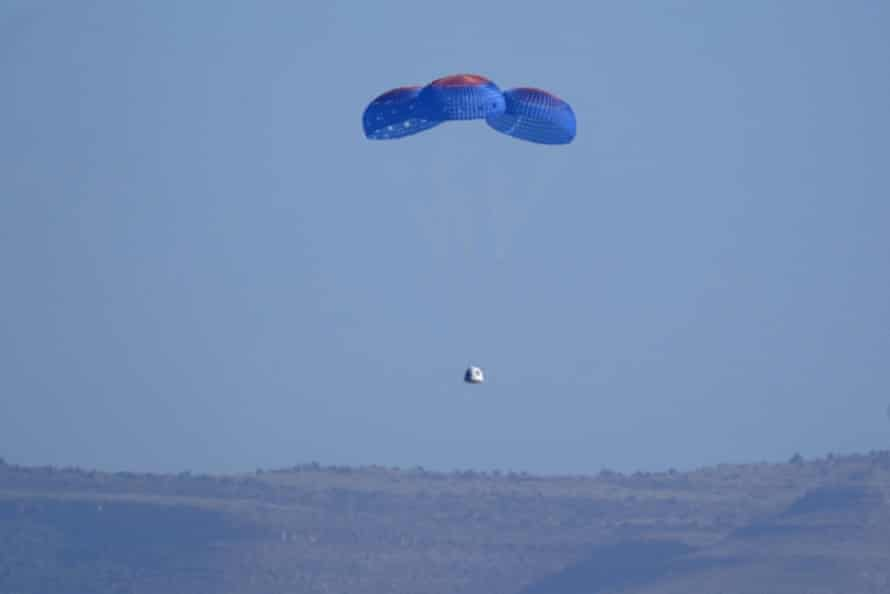 Parachutes carry the Blue Origin capsule with passengers William Shatner, Chris Boshuizen, Audrey Powers and Glen de Vries down to the spaceport near Van Horn, Texas, on Wednesday.