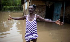 A woman in front of her home flooded by heavy rains brought on by Hurricane Irma in Fort-Liberté, Haiti
