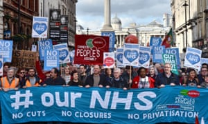 A group of demonstrators protesting against further funding cuts to the NHS marches down Whitehall.