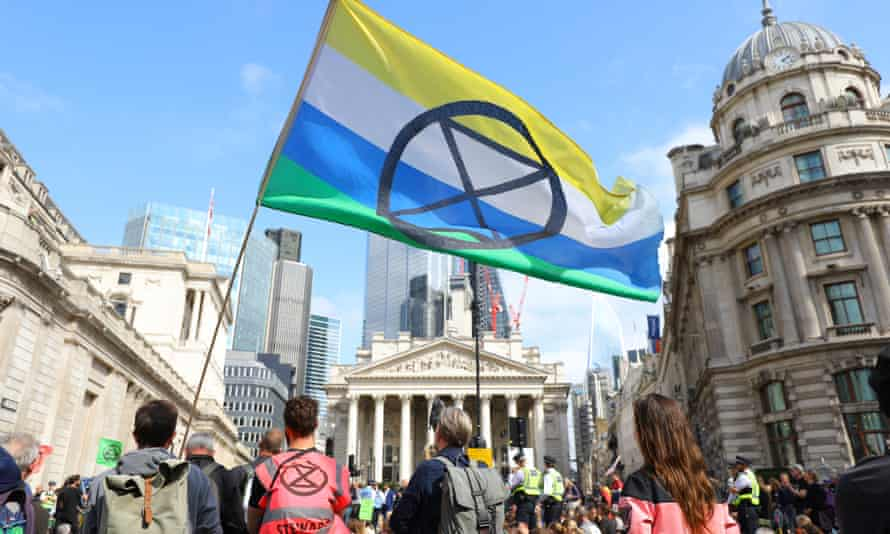 Extinction Rebellion demonstrators with XR flag at Bank junction in front of the Bank of England in the City of London.