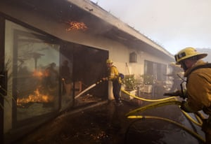 Firefighters try to extinguish flames at a house in the Bel Air district of Los Angeles