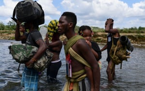 Darien, Panama. Migrants cross the Chucunaque river after walking for five days in the Darien Gap on their way to the US. Migrants remain stranded at the Panama-Colombia border, while the country is expecting a new influx of migrants