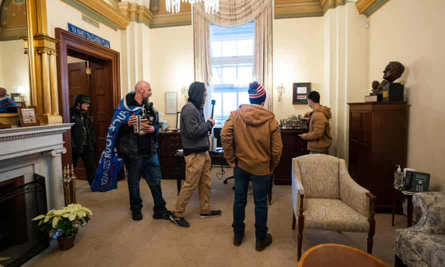 Donald Trump supporters stand in the office of House speaker Nancy Pelosi, where a laptop was stolen.