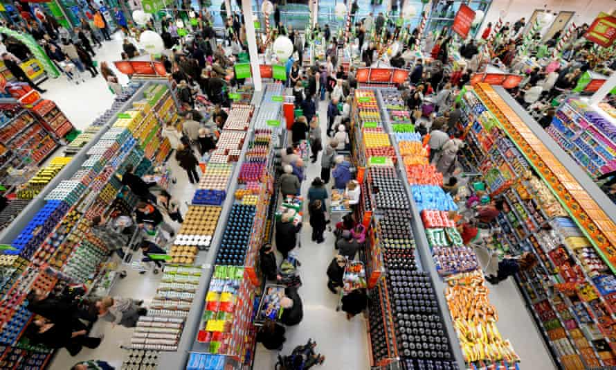 Shoppers crowd the aisles in a busy supermarket.