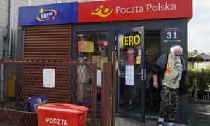 Aa man wearing a face mask leaves a post office in Warsaw amid the coronavirus pandemic.