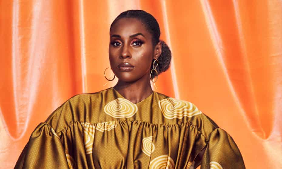 Issa Rae in a gold dress against an orange backdrop