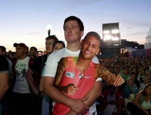 A Brazil fan with a cardboard cutout of Neymar