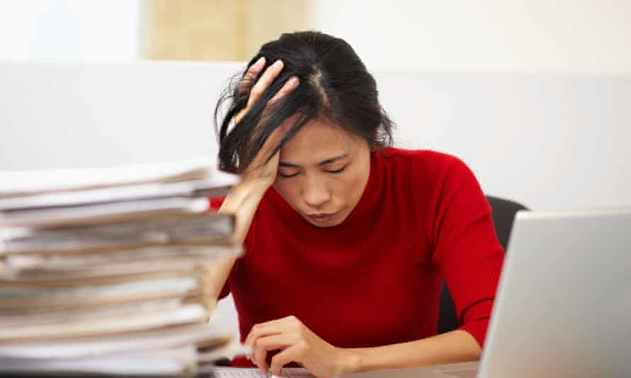Businesswoman at desk with her head in her hands