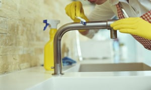 Woman cleaning kitchen tap with toothbrush, close-up. Obsessive compulsive, perfectionist, cleaner