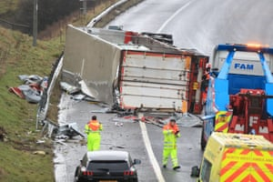Recovery workers prepare to recover an overturned lorry at the scene of an accident on the eastbound track of the M62 motorway between junctions 21 (Milnrow) and 22 (Ripponden)