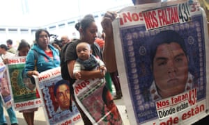 "Relatives of the missing students hold signs that read in Spanish ""We are missing 43 – where are they?"" after they listened to the international experts' report, in Mexico City Sunday."