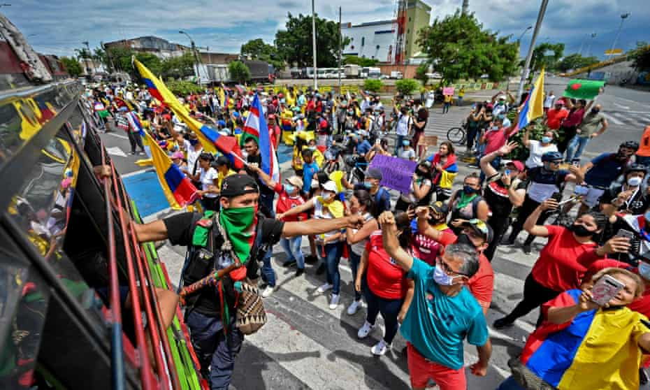 Indigenous guard Abner Bisus, left, 27, takes part in a protest against the government of Colombian President Iván Duque, in Cali, last week.