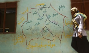 A Sudanese woman walks past a map of Sudan at a polling station in Khartoum.