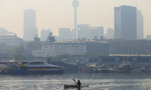 A paddler is seen as smoke haze drifts over the CBD in Sydney