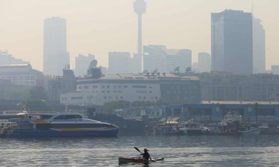 A paddler is seen as smoke haze drifts over the CBD in Sydney