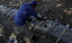 A gravedigger paints numbers on crosses at the Sao Francisco Xavier cemetery in Rio de Janeiro during the coronavirus pandemic.