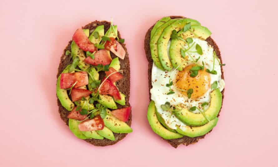 Toasts of dark bread with avocado slices, red tomatoes, fried egg and microgreen. Top view with pink background.