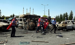 People walk next to destroyed cars outside the presidential palace in Ankara, Turkey