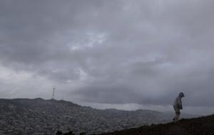 A man walks in rain and hail up Bernal Heights