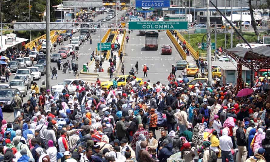 Venezuelans queue to register their exit from Colombia before entering into Ecuador at Rumichaca Bridge.