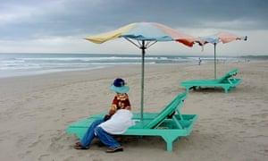A woman sits on an empty beach chair in Kuta beach, Bali, Indonesia