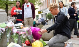A man lays flowers in St Ann's Square