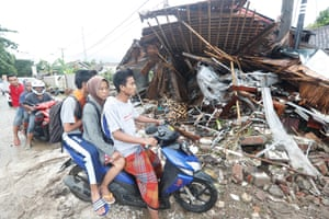 Local residents on a scooter transit near debris after a tsunami hit the Sunda Strait in Pandeglang, Banten, Indonesia