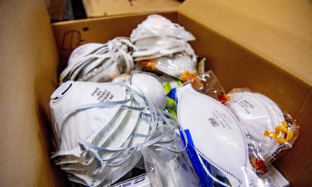 Protective face masks stacked in a cardboard box