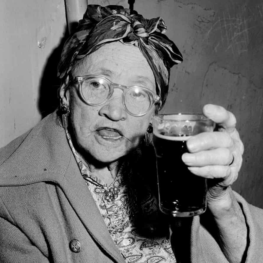 A woman drinks a pint of beer in a Glebe pub on the eve of its closing in 1967.