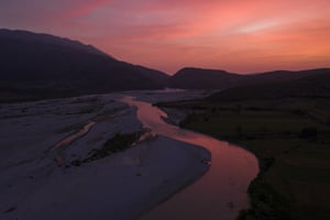 The sun sets behind the Vjosa River near Tepelene, Albania