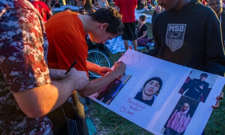 Students sign a poster with photos of Joaquin Oliver, one of those killed in the shooting at Marjory Stoneman Douglas high school on 14 February 2018.