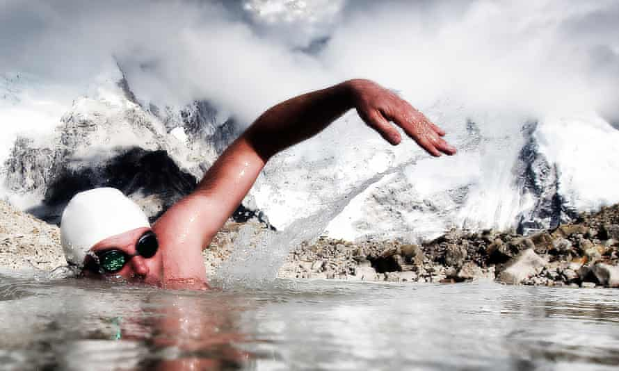 Man swims in icy water with swimming goggles and cap