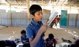 A child reads a book in a makeshift school run by Rohingya teachers in Kutupalong refugee camp in Cox's Bazar, Bangladesh.