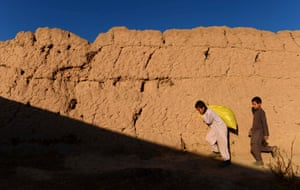 Afghan children carry materials as they walk on the outskirts of the city of Herat.